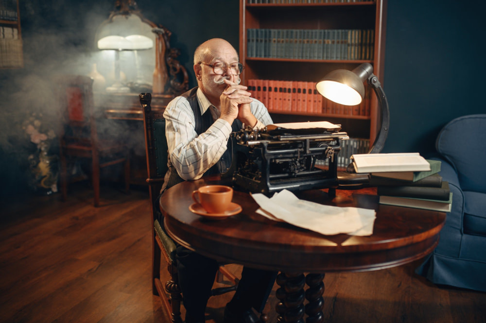 Elderly writer thinks at vintage typewriter